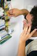 portrait d'un éléctricien au téléphone devant un disjoncteur