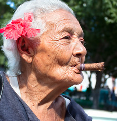 Old wrinkled woman smoking cigar