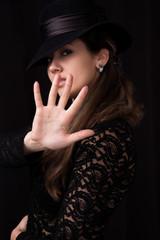 women in black hat showing stop
