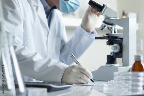 Scientist conducting research with microscope - 21497085