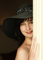Beautiful brunette woman in hat looking from behind a curtain