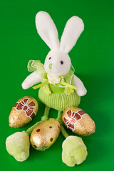 easter bunny and three golden eggs on green background