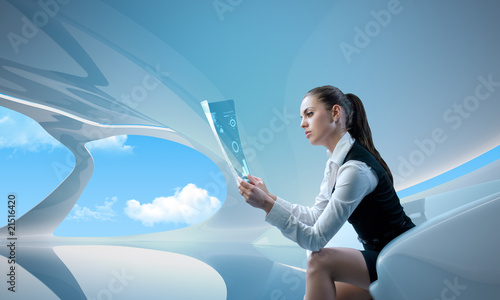 Sexy businesswoman examining future digital report / newspaper