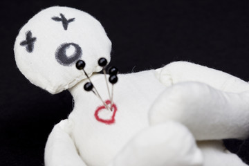 White voodoo doll with pins in its heart