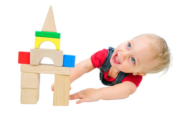 Little cute boy builds houses out of colored blocks
