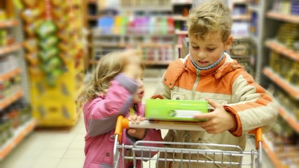 boy and girl with shopping trolley looks at box in supermarket