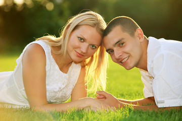 Young happy couple lying down on grass