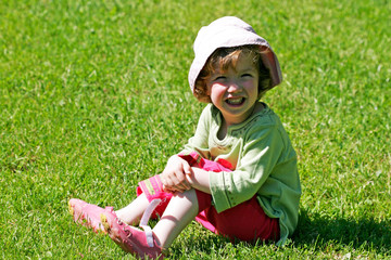 petite fille assise dans l'herbe