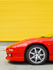 Side view of a front of red sportcar on yellow background