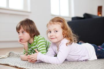 junge und mädchen liegen auf teppich