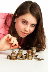 A woman watching stacks of coins