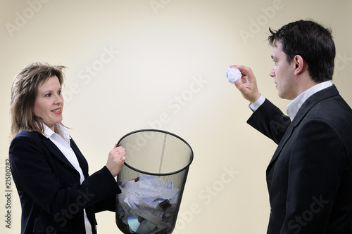 business man and woman throwing papers in office basket