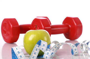 Green apple with measuring tape on the background of dumbbells
