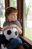 Boy wants to play soccer on a rainy day