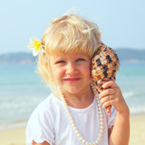 pretty little girl has lean seashell bowl to an ear on seacoast