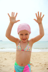 Funny little girl wearing swimsuit on a beach