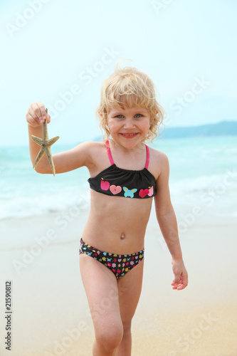 Happy funny girl on the beach with starfish