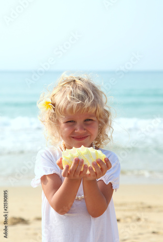pretty girl with a seashell on the beach- vacation