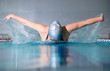 woman swims using the butterfly stroke in indoor pool