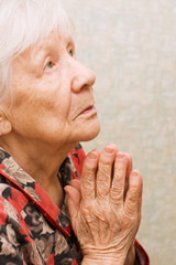 The old woman prays in a room