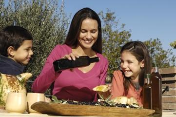 figli e madre con l'olio biologico