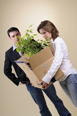 fired woman holding package with documents and green plant