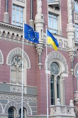 EU and ukrainian flags near National Bank of Ukraine