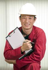 Engineer in helmet, working in office