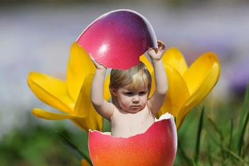Kleinkind springt aus Osterei