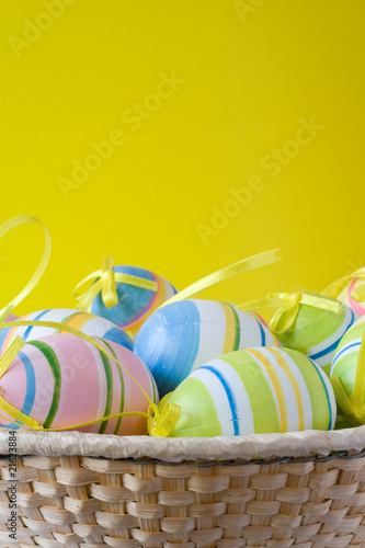 punnet with colorful easter eggs on yellow background