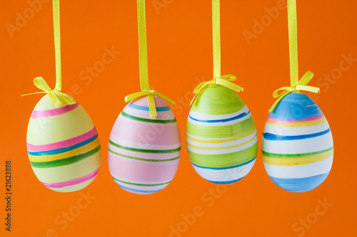 four colorful easter eggs isolated on orange background