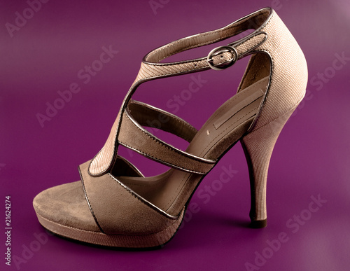 Elegant beige high heeled shoe on purple background