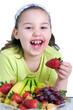 Mädchen nascht Erdbeere vom Obstteller