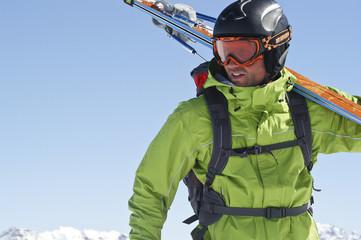 Skifahrer trägt seine Skier