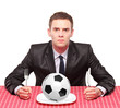 A businessman sited on a table with a ball in his plate