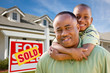 Father with Son In Front of Real Estate Sign and Home