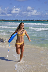 teenage girl with boogieboard at kailua beach, hawaii