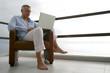 homme assis sur une terrasse devant ordinateur portable
