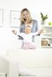 junge mutter mit baby auf weißem sofa