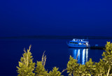 Motor yacht moored to jetty at night poster