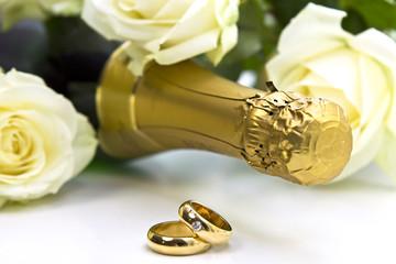 goldene Eheringe mit Champagner und Rosen