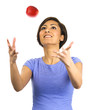 Young woman tosses an apple into the air.
