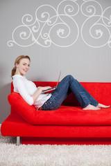 frau mit laptop auf rotem sofa