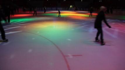 people skating in night skating rink with dynamic illumination