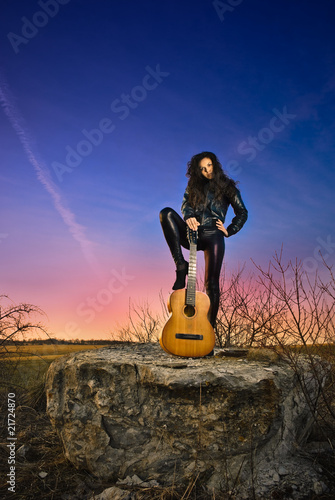 woman with guitat at sunset rock