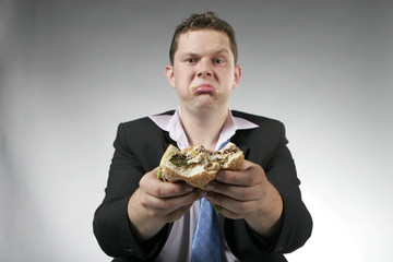 Unhappy businessman eating burger
