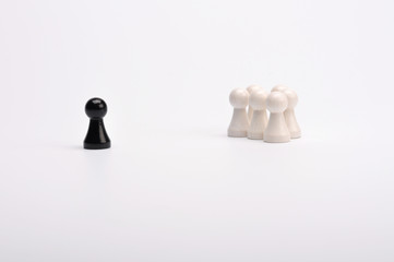 Schwarze Figur im Abstand zu einer Gruppe weisser Figuren