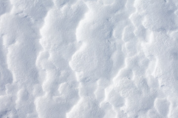 By wind and sun weathered snow surface, background pattern