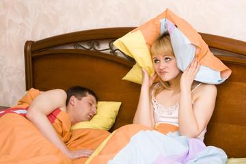 Woman awaking by her husband snoring