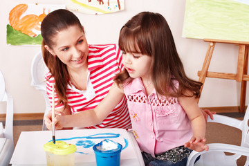 Child with teacher draw paints in play room. Child care.